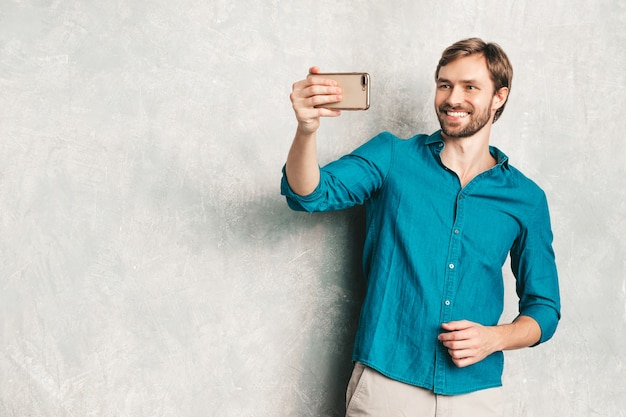 Portrait of handsome smiling hipster lumbersexual businessman model wearing casual jeans shirt clothes.