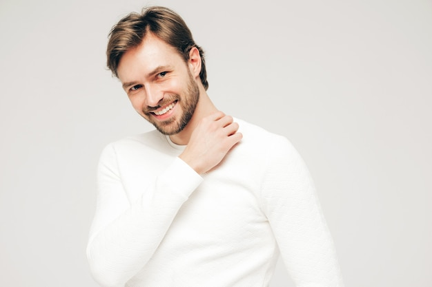 Portrait of handsome smiling hipster lumbersexual businessman model wearing casual white sweater and trousers