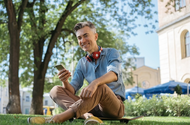 Portrait of handsome smiling man holding mobile phone