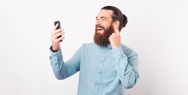 Portrait of handsome smiling man wearing blue shirt using phone and earpods