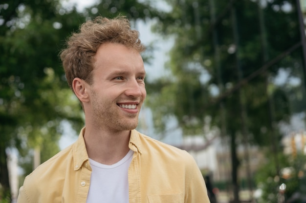 Portrait of handsome smiling man wearing casual shirt looking away standing on the street