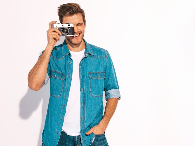 Portrait of handsome smiling man wearing summer jeans clothes. model male holding vintage photo camera.