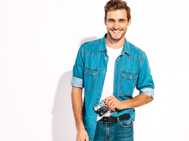 Portrait of handsome smiling man wearing summer jeans clothes. model male taking picture on old vintage photo camera.