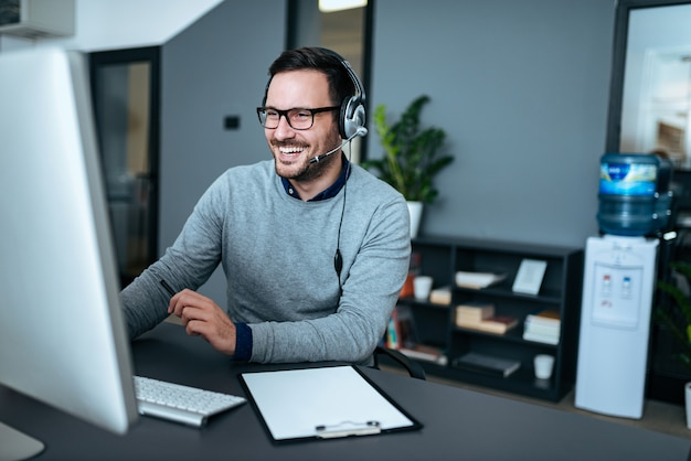 Portrait of a handsome smiling man with headset working on the computer.