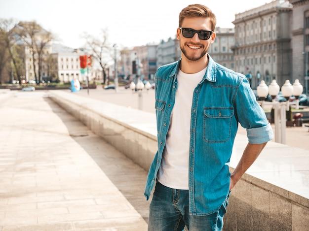 Ritratto del modello dell'uomo d'affari lumbersexual sorridente alla moda bello dei pantaloni a vita bassa. uomo vestito con abiti giacca di jeans.