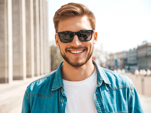 Portrait of handsome smiling stylish hipster lumbersexual businessman model. man dressed in jeans jacket clothes.