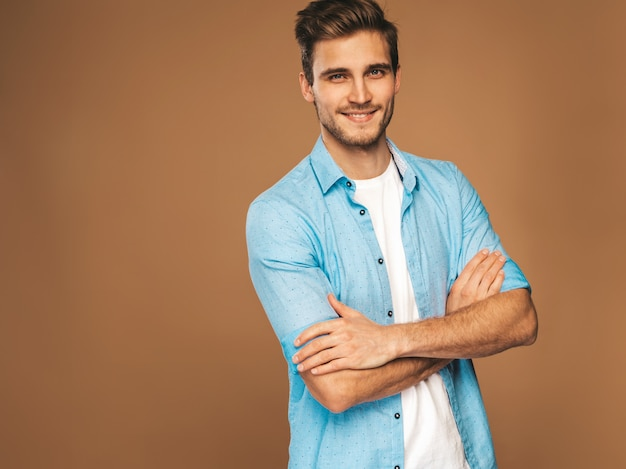 Portrait of handsome smiling stylish young man model dressed in jeans clothes. fashion man. posing