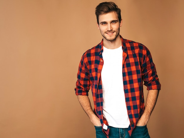 Portrait of handsome smiling stylish young man model dressed in red checkered shirt. fashion man posing