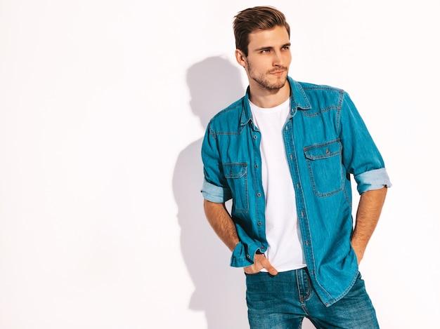 Il ritratto dei jeans d'uso d'uso di modello alla moda sorridenti bei del giovane copre. uomo di moda