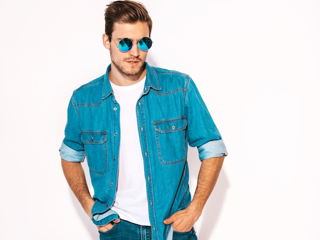 Portrait of handsome smiling stylish young man model wearing jeans clothes and sunglasses. fashion man