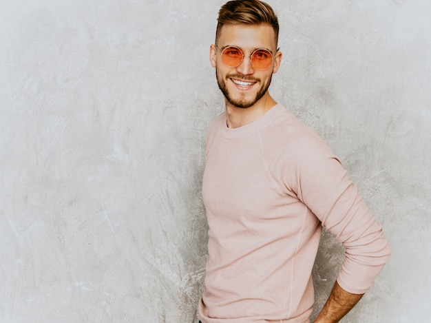 Portrait of handsome smiling young man model wearing casual summer pink clothes. fashion stylish man posing in round sunglasses