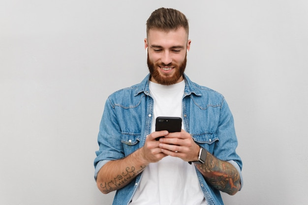 Portrait of a handsome smiling young man wearing casual clothes standing isolated over gray wall, listening to music with wireless earphones, holding mobile phone