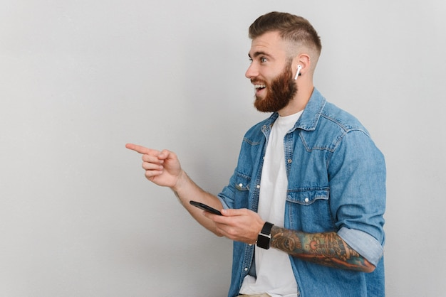 Portrait of a handsome smiling young man wearing casual clothes standing isolated over gray wall, listening to music with wireless earphones, pointing finger away
