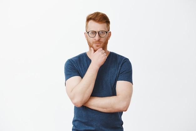 Ritratto di bello stratega con capelli rossi e setole, tenendo la mano sulla barba e fissando concentrato