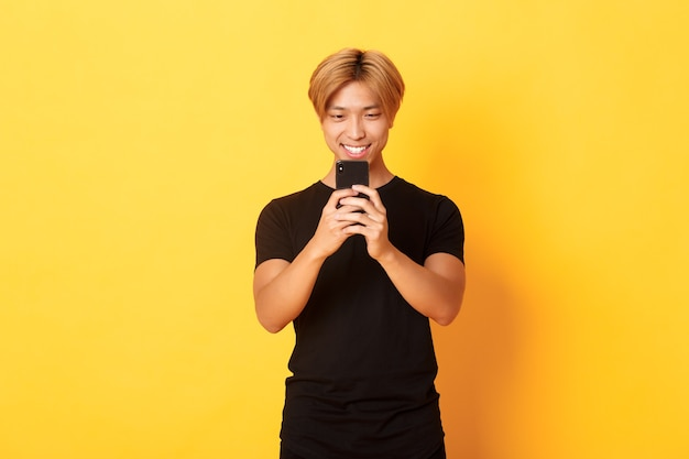 Portrait of handsome stylish asian guy with blond hair, using mobile phone and smiling, messaging in smartphone app, yellow wall