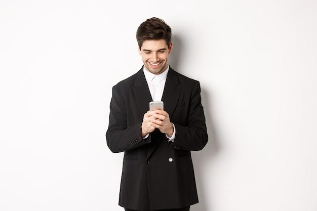 Ritratto di uomo d'affari bello ed elegante in abito nero, scrivendo un messaggio, sorridendo e guardando smartphone, in piedi su sfondo bianco.