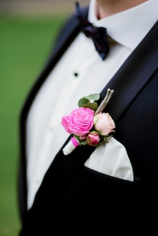 Portrait of handsome stylish groom with pink boutonniere