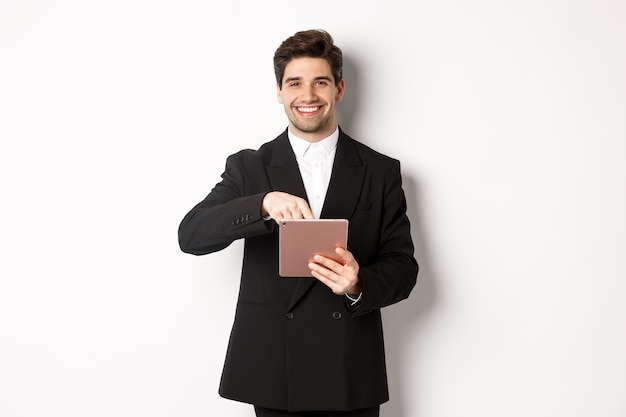 Portrait of handsome, stylish male entrepreneur in black suit pointing at digital tablet, showing something online, standing against white background