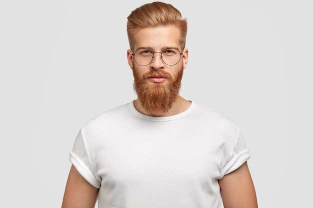 Portrait of handsome stylish man with trendy hairdo, looks seriously
