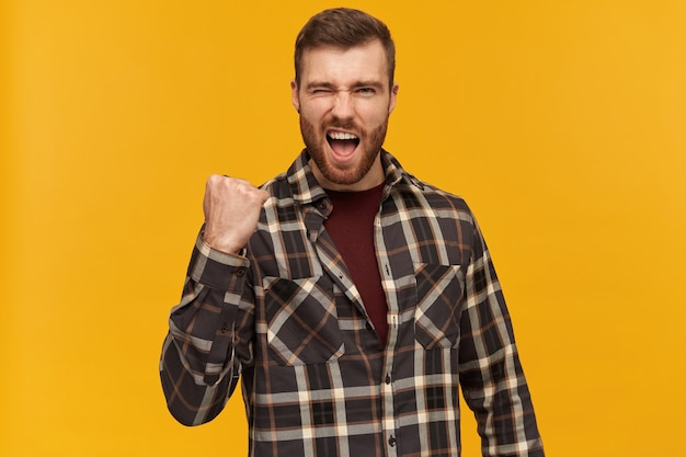 Portrait of handsome, successful male with brunette hair and bristle. wearing checkered shirt and accessories. raises fist in celebration, isolated over yellow wall