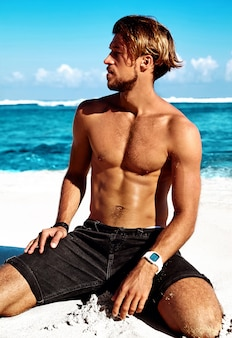 Portrait of handsome sunbathed fashion man model posing on summer beach with white sand on blue sky