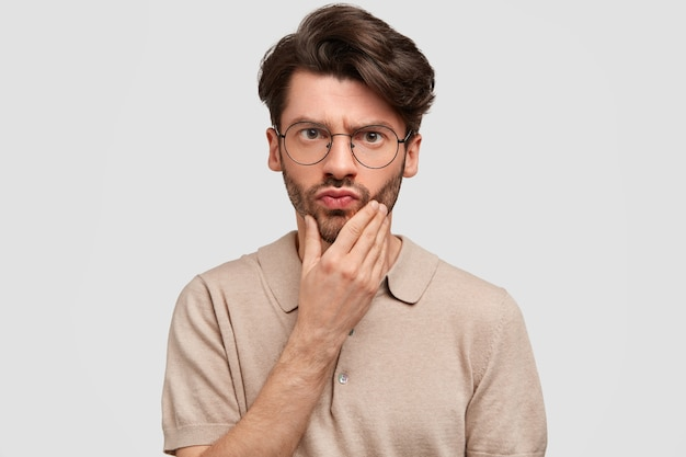 Portrait of handsome surprised bearded male looks scrupulously at camera