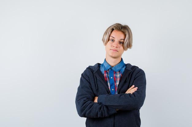 Ritratto di un bel ragazzo adolescente che tiene le braccia conserte in camicia, felpa con cappuccio e sembra fiducioso in vista frontale