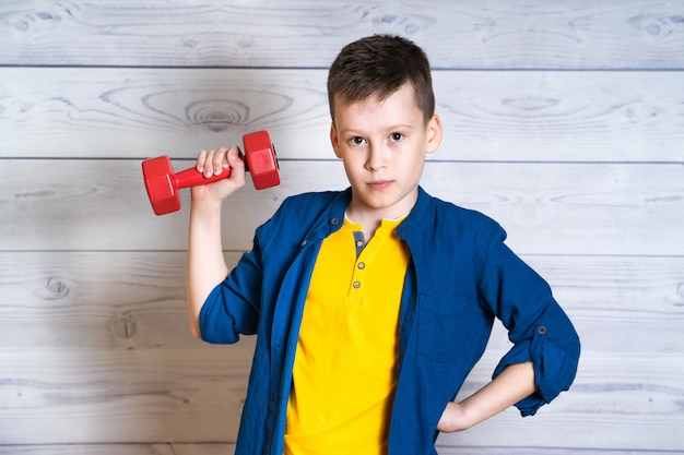 Portrait of a handsome teenage boy with dumbbell