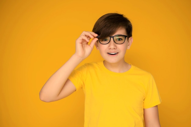 Portrait of a handsome teenager 12-13 years old on a yellow background.