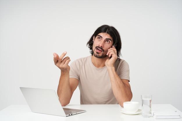 Ritratto di uomo d'affari bello e premuroso con barba e capelli neri. concetto di ufficio. parla al telefono e gesticola. seduto sul posto di lavoro, isolato su un muro bianco