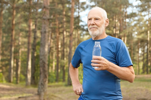 Portrait of handsome tired european senior elderly male in t-shirt holding glass bottle, enjoying fresh drinking water after running exercise in forest, catching his breath, looking around