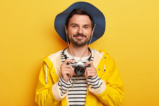 Portrait of handsome unshaven man holds retro camera, takes pictures of something, wears hat, striped jumper and raincoat, isolated over yellow wall