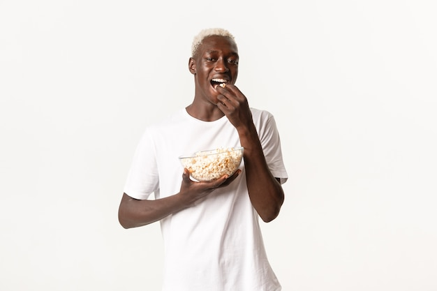 Portrait of handsome young african-american blond guy enjoying watching tv series or movie at home, eating popcorn from glass bowl