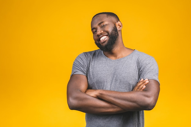 Portrait of handsome young african american man smiling isolated yellow wall.