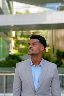 Portrait of handsome young african businessman thinking outdoors