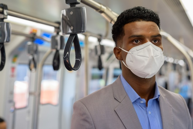Portrait of handsome young african businessman wearing suit and face mask