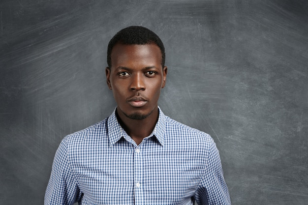 Portrait of handsome young african school teacher wearing checkered shirt getting ready for lesson, making up his mind, looking with serious and confident face expression, standing at blank chalkboard