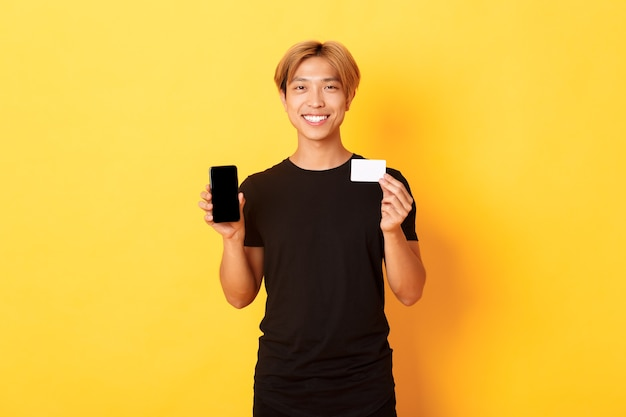 Portrait of handsome young asian guy showing smartphone screen, banking app and credit card, standing yellow wall and smiling.