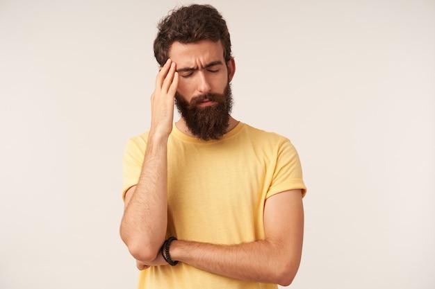 Ritratto di bel giovane uomo barbuto con gli occhi chiusi in piedi contro il muro bianco braccio tocco barba emozione dubbioso pensatore mal di testa