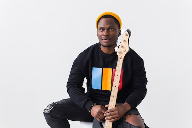 Portrait handsome young black man dressed in jeans and sweatshirt with guitar on white surface