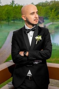 Portrait of handsome young bridegroom in black suit looking away