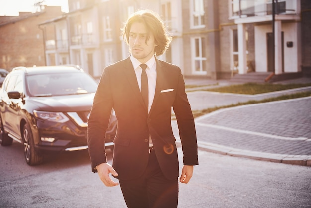 Portrait of handsome young businessman in black suit and tie outdoors near modern car in the city.