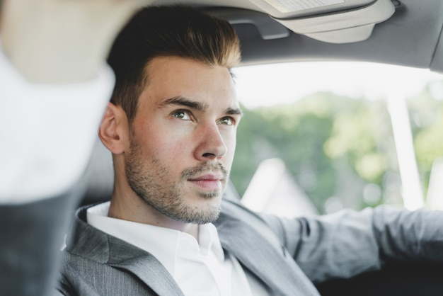 Portrait of handsome young businessman in the car