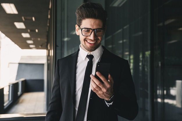Portrait of handsome young businessman dressed in formal suit standing outside glass building, and holding mobile phone