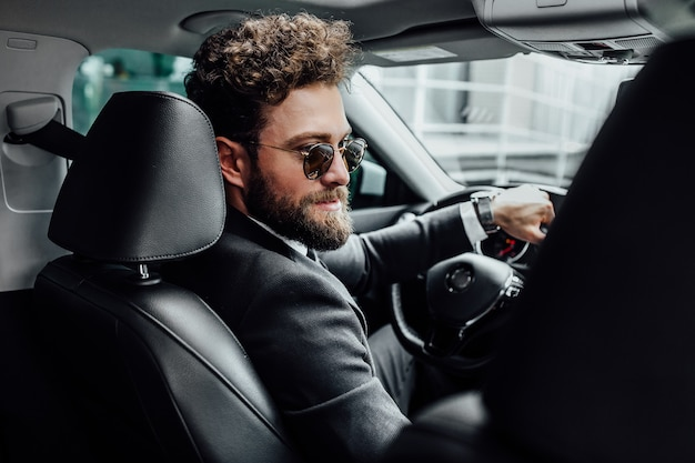 Portrait of handsome young businessman in full suit in sunglasses driving a new car