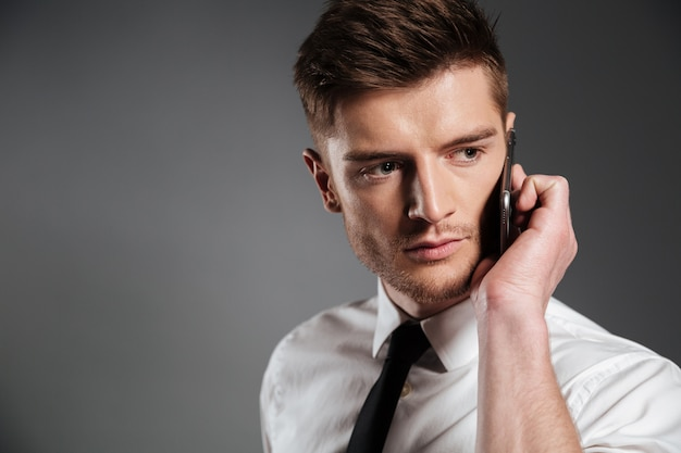 Portrait of a handsome young businessman talking on mobile phone