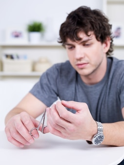 Portrait of handsome young candid man cutting nails - indoors