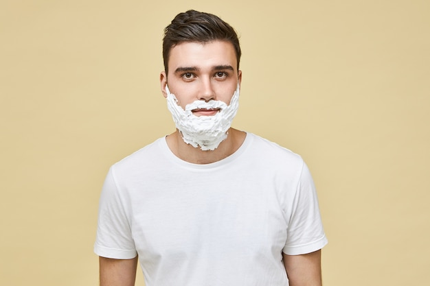 Portrait of handsome young caucasian brunette man posing isolated with white shave foam applied on his face, preparing skin for shaving. morning routine, masculinity, beauty and care concept