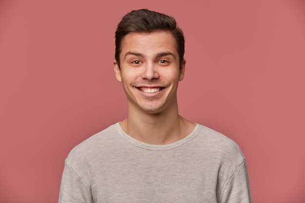 Portrait of handsome young cheerful man wears in blank long sleeve, looks at the camera with happy expressions, stands over pink background.