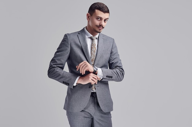 Portrait of handsome young confident arabic businessman with fancy mustache in fashion gray full suit adjusting his sleeve on studio background